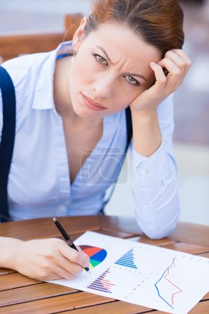Unhappy business woman looking displeased working on financial report