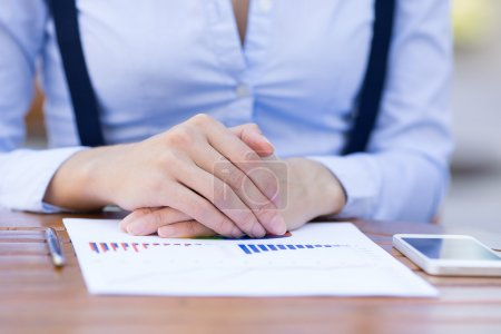 Businesswoman hands sitting at table in front of financial report document with graphs