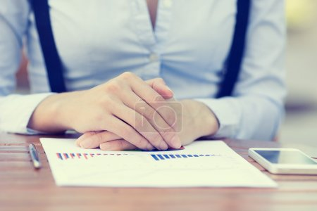 Photo for Closeup cropped image business woman hands, executive sitting at table in front of financial report document with graph, charts, diagram ready to discuss company results, profits. Stock market concept - Royalty Free Image