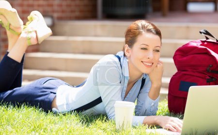 Female student lying down on lawn grass working on laptop