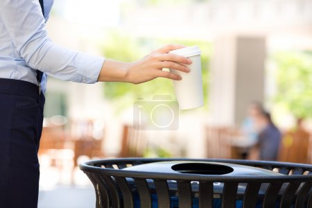 Photo for Closeup cropped image woman's hand throwing empty paper coffee cup in recycling bin, isolated outside, trees background. Recycling, eco friendly approach concept. Keep streets, city, earth clean - Royalty Free Image
