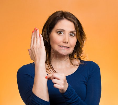 Woman pinching her arm skin, giving reality check gesture