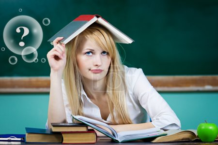 Student sitting at desk in classroom looking upwards, confused, thinking
