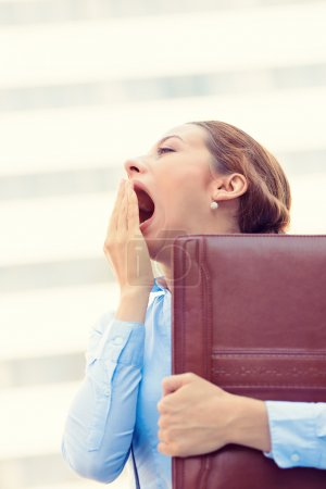 Sleepy young business woman, running to work wide open mouth yawning