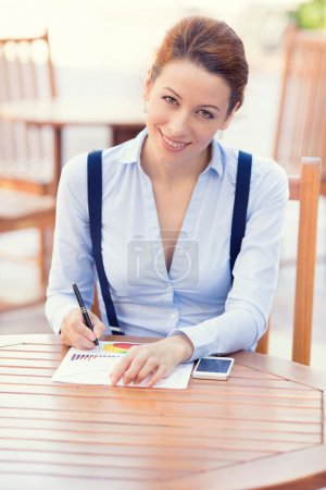 Happy businesswoman working outdoors on financial report