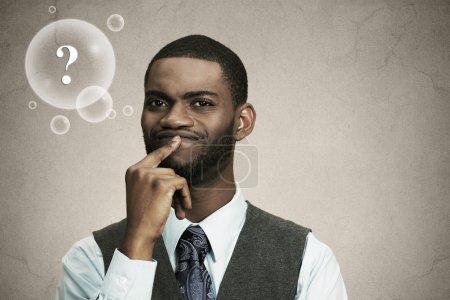 Photo pour Gros plan portrait jeune, perplexe homme d'affaires penser, décider profondément sur quelque chose doigt sur les lèvres regardant fond noir isolé confus avec bulle question. Émotion expression faciale sentiment - image libre de droit