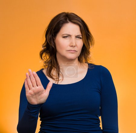Photo for Closeup portrait middle aged, annoyed woman with bad attitude, giving talk to hand gesture with palm outward, isolated orange background. Negative emotion, facial expression feelings, body language - Royalty Free Image