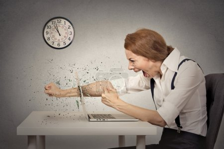 Photo for Angry, furious businesswoman throws a punch into computer, screaming. Negative human emotions, facial expressions, feelings, aggression, anger management issues - Royalty Free Image