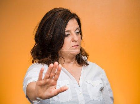 Photo pour Offensé. Portrait femme grincheuse d'âge moyen avec une mauvaise attitude donnant parler à mon geste de la main avec la paume vers l'extérieur, fond orange isolé. Émotions négatives, sentiments d'expression faciale, langage corporel - image libre de droit