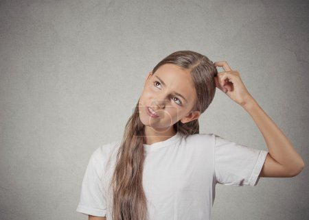 Photo for Confused, remembering. Portrait teenager girl scratching head, thinking daydreaming about something, looking up isolated grey wall background. Human facial expression, emotion, feeling body language - Royalty Free Image