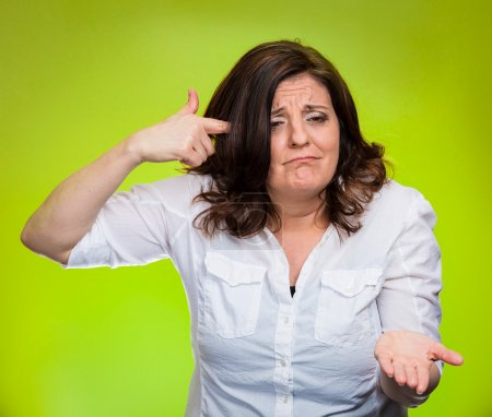 Photo for Closeup portrait angry mad middle aged woman gesturing with her finger against temple asking are you crazy? Isolated yellow background. Negative human emotions facial expression feeling body language - Royalty Free Image