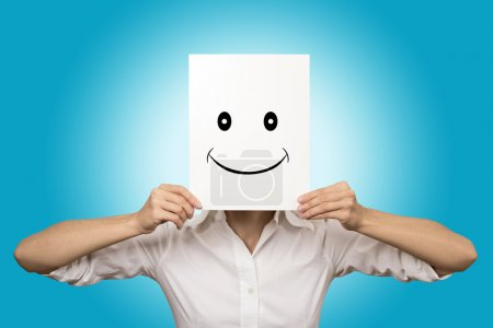 Woman covering face with smiling paper mask