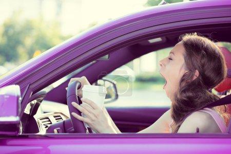 Photo pour Closeup portrait endormi, fatigué, fatigué, épuisé jeune jolie femme au volant de sa voiture après de longues heures de trajet, isolé fond du trafic routier. Transports, manque de sommeil, notion d'accident - image libre de droit