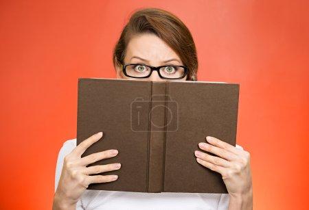 Frau mit Brille versteckt Gesicht hinter Buch
