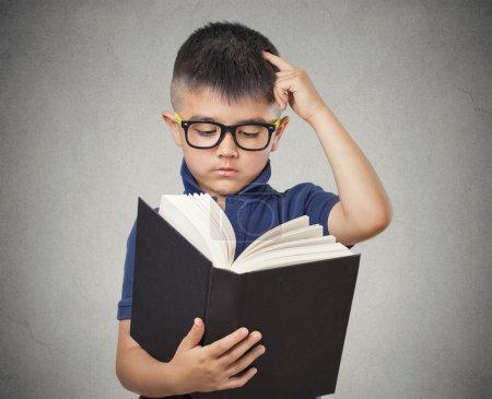 Photo pour Enfant portrait agrandi avec des lunettes de lecture de livre, isolé mur gris fond. expressions de visage. concept de l'éducation - image libre de droit