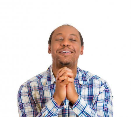 young man praying hands clasped hoping for best