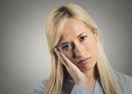Photo for Depressed gloomy. Closeup portrait unhappy young woman head on hand bothered by mistake situation having bad headache isolated grey wall background. Negative human emotion facial expression feeling - Royalty Free Image