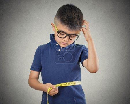 child measuring his waistline