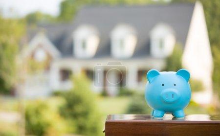 Foto de Venta de bienes raíces, ahorros para el hogar, concepto de mercado de préstamos. Plan hipotecario de la industria de la vivienda y estrategia de ahorro de impuestos residenciales. Hucha aislada fuera de casa en segundo plano. Concéntrate en Piggybank. Propietario - Imagen libre de derechos