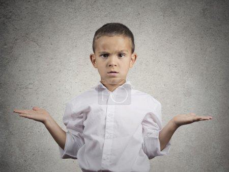 Photo pour Closeup portrait désemparés, malheureux enfant garçon avec bras demandant quel est le problème qui se soucie, alors quoi, je ne sais pas fond isolé mur gris. l'émotion humaine négative facial expression gestuelle - image libre de droit