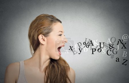 Photo for Side view portrait woman talking with alphabet letters coming out of her open mouth isolated grey wall background. Human face expressions, emotions. Communication, information, intelligence concept - Royalty Free Image