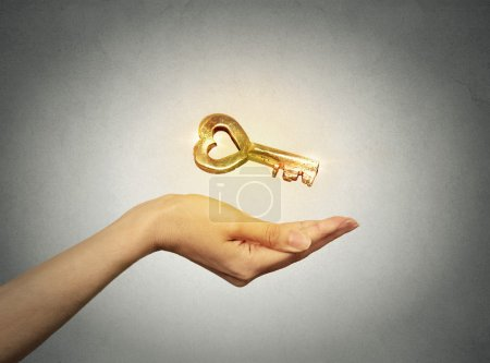 woman hand holding offering new golden key