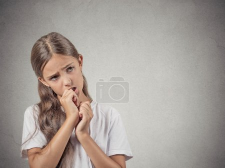 Photo for Closeup portrait teenager girl with finger in mouth, sucking thumb, biting fingernail in stress, clueless, isolated grey wall background. Negative emotion facial expression feeling. Body language - Royalty Free Image
