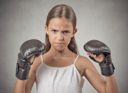 Aggressive child teenager girl wearing boxing gloves