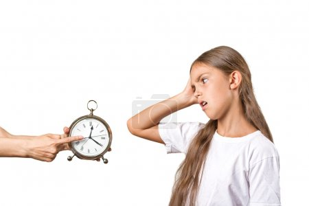 Photo pour Les enfants doivent se coucher. Portrait maman montrant horloge fille qu'il est tard. Elle n'aime pas le fond blanc isolé. Expression du visage émotions. Concept parental difficile. Horaire des enfants - image libre de droit