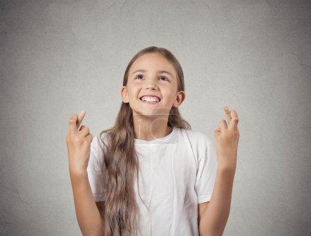 smiling hopeful girl crossing her fingers hoping