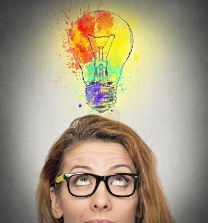 Photo pour Femme ayant idée brillante ampoule colorée au-dessus de la tête, fond mural gris isolé. Expressions du visage humain, émotions, sentiments. Créativité, imagination, dynamisme, concept d'intelligence - image libre de droit