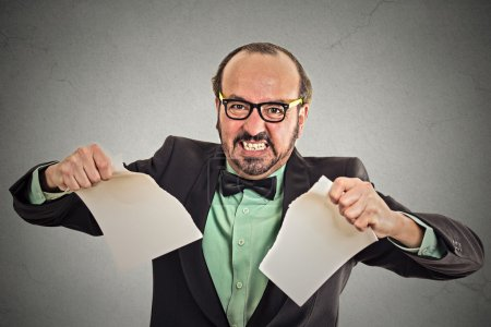 angry businessman tearing a document to pieces