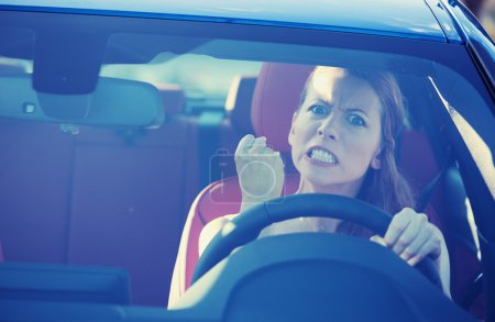 Photo for Portrait displeased angry pissed off aggressive woman driving car, shouting at someone in traffic hand fist up in air front windshield view. Emotional intelligence concept. Negative human expression - Royalty Free Image