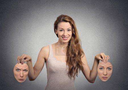 Photo pour Portrait belle fille heureuse tient deux masques isolé fond de mur gris. Expressions du visage humain, émotions, sentiments, état d'esprit bipolaire concept - image libre de droit