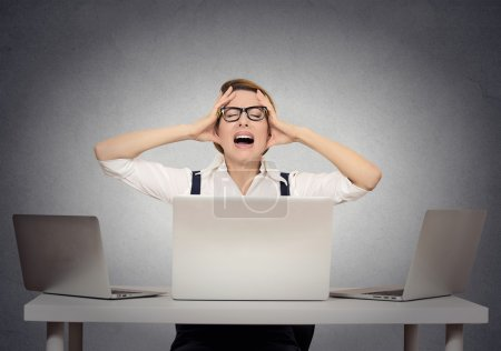 Photo for Stressed businesswoman sitting at table in front of multiple computers in her office having nervous breakdown. Negative human face expressions, emotion feeling body language - Royalty Free Image