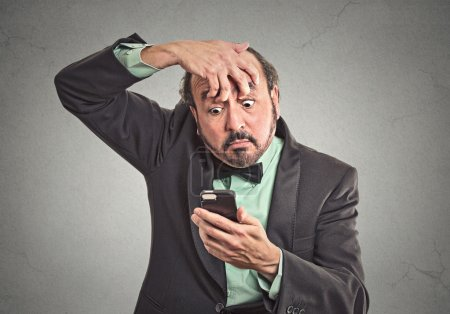 Photo for Closeup portrait sleepy funny looking middle aged man fingers keep eyes open low energy trying to stay awake holding smart phone isolated grey background. Negative facial expression emotion feeling - Royalty Free Image