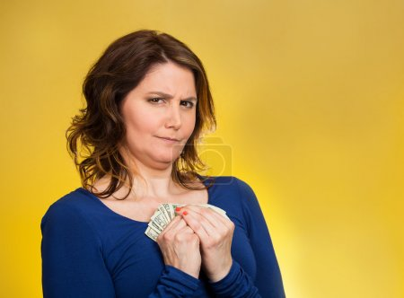 Photo for Closeup portrait greedy middle aged woman corporate business employee, worker, student holding dollar banknotes tightly isolated orange background. Negative human emotion facial expression feeling - Royalty Free Image