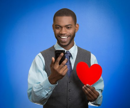 Man looking at smart phone holding red heart