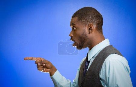 Photo pour Plan rapproché côté portrait de profil beau jeune homme pointant l'index à quelque chose stupéfait dumbstruck regardant quelqu'un geste fond bleu isolé. Réaction humaine d'expression faciale d'émotion - image libre de droit