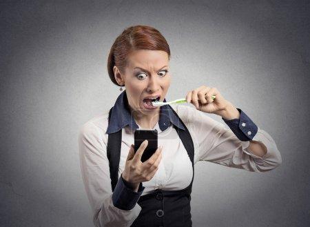 Shocked woman reading news on smartphone brushing teeth