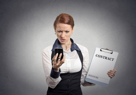 Photo for Portrait unhappy skeptical businesswoman holding contract document looking reading news on smart mobile phone isolated office grey wall background. Human face expression emotion of corporate executive - Royalty Free Image