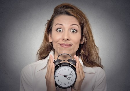 Business woman holding alarm clock waiting