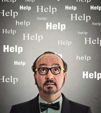 Photo pour Man needs help. Headshot middle aged business man with glasses looking up thinking help words above head isolated grey wall background. Human face expression emotion life perception - image libre de droit
