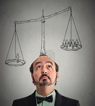 Photo pour Un homme, homme d'affaires avec échelle au-dessus de tête plusieurs groupes hors des gens d'affaires sur un équilibre de pondération. Alimentation, avis, leadership, l'importance de soi, notion d'ego. Expression du visage pensif, émotion - image libre de droit