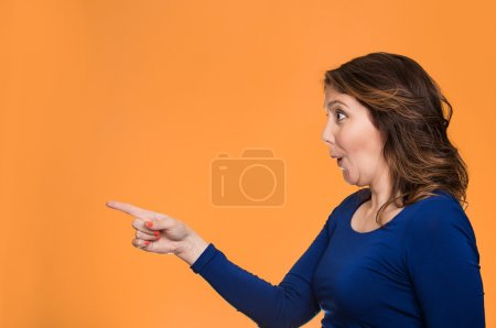 Photo pour Side view profile portrait excited casual female pointing out at copy space isolated over orange background. Human face expression, emotion, reaction, feeling - image libre de droit