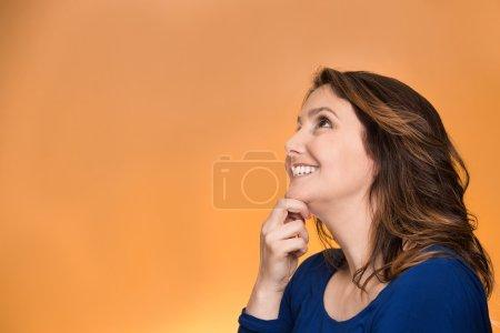 Photo pour Verticale de profil de vue de côté pensif de femme heureuse souriant recherchant la rêverie d'isolement au-dessus du fond orange. Expressions positives du visage humain, émotions, sentiments, perception - image libre de droit