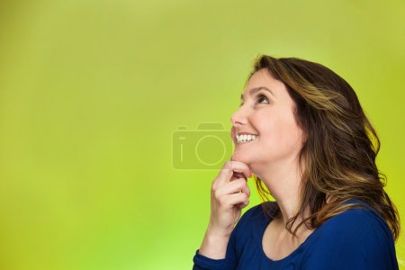 Photo for Side view profile portrait thoughtful happy woman smiling looking up daydreaming isolated over green background. Positive human face expressions, emotions, feelings, perception - Royalty Free Image