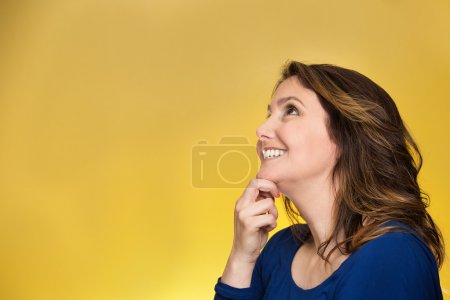 Photo pour Side view profile portrait thoughtful happy woman smiling looking up daydreaming isolated over yellow background. Positive human face expressions, emotions, feelings, perception - image libre de droit