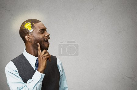 Photo pour Side view profile headshot happy man thinking found solution for problem isolated grey wall background with copy space light bulb. Human face expression emotion feeling body language perception iq - image libre de droit