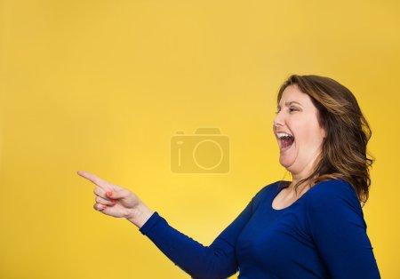 Photo pour Vue latérale portrait profil âge moyen excité heureux rire femme pointant du doigt quelque chose quelqu'un isolé fond jaune avec de l'espace de copie. Émotion humaine positive réaction d'expression du visage - image libre de droit